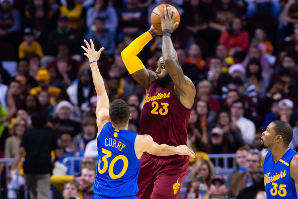 LeBron James #23 of the Cleveland Cavaliers passes while under pressure from Stephen Curry #30 of the Golden State Warriors