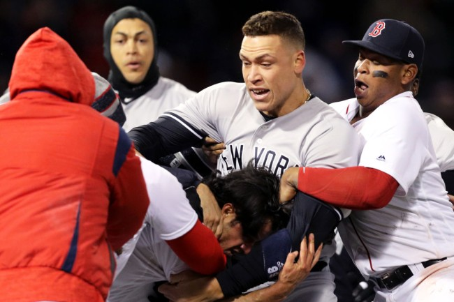 BOSTON, MA - APRIL 11: From top left, Giancarlo Stanton #27 of the New York Yankees, Aaron Judge #99 of the New York Yankees and Rafael Devers #11 of the Boston Red Sox separate Joe Kelly #56 of the Boston Red Sox, bottom, from Tyler Austin #26 of the New York Yankees, not pictured, during a fight in the seventh inning at Fenway Park on April 11, 2018 in Boston, Massachusetts. Austin rushed the mound after being struck by a pitch from Kelly.