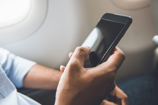 holding cellphone on airplane