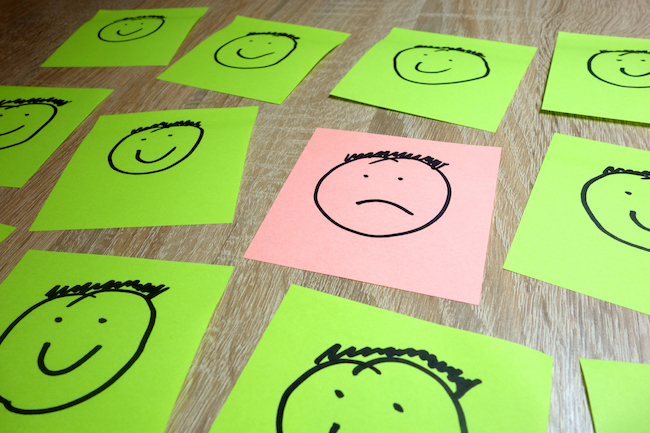 Single sad face drawing among happy smiling ones