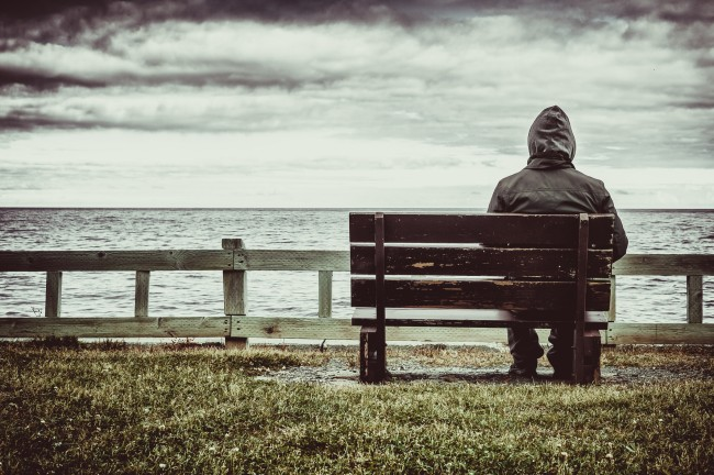lonely Man sitting on bench overlooking sea