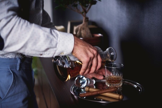 Unrecognizable man pouring a glass of whiskey