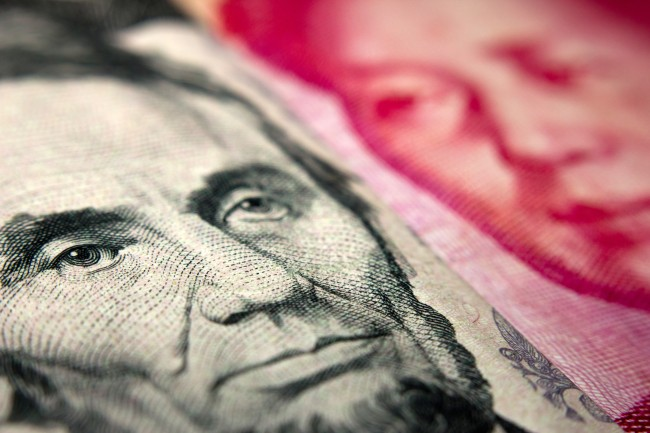 Close-up of an American banknote (showing Lincoln) and a Chinese yuan banknote (Mao Zedong)