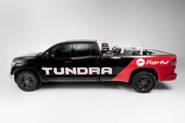 """Toyota collaborated with its Plano, Texas, neighbor, Pizza Hut, and Nachi Robotic Systems to create an automated pizza-making vehicle. The Tundra PIE Pro is built to run entirely on a hydrogen fuel cell electric power unit adapted from the Toyota Mirai, which both drives the vehicle forward and powers the self-contained """"Kitchen"""" built into the truck's bed."""
