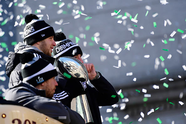 PHILADELPHIA, PA - FEBRUARY 08: (L-R) Quarterbacks Nick Foles #9, Nate Sudfeld #7 and Carson Wentz #11 of the Philadelphia Eagles, acknowledge fans as Sudfeld hoists the Vince Lombardi Trophy atop a parade bus during festivities on February 8, 2018 in Philadelphia, Pennsylvania. The city celebrated the Philadelphia Eagles' Super Bowl LII championship with a victory parade. (Photo by Corey Perrine/Getty Images)