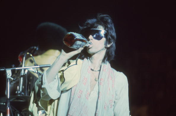 Guitarist Keith Richards having an alcohol drink while on stage during the Rolling Stones' 1975 Tour of the Americas. (Photo by Christopher Simon Sykes/Hulton Archive/Getty Images)
