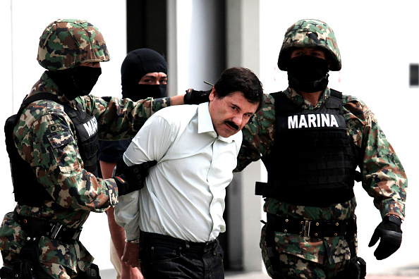 """Mexican Navy soldiers escort Joaquin Guzman Loera (front), alias """"El Chapo Guzman"""", leader of the Sinaloa Cartel, during his show up in front of the press, at the Mexican Navy hangar in Mexico City, capital of Mexico, on Feb. 22, 2014. Mexican President Enrique Pena Nieto on Saturday confirmed the capture of the world's most wanted drug lord, Joaquin Guzman Loera, known as El Chapo, in the Pacific resort of Mazatlan. (Photo by Jair Cabrera Torres/NurPhoto) (Photo by NurPhoto/Corbis via Getty Images)"""