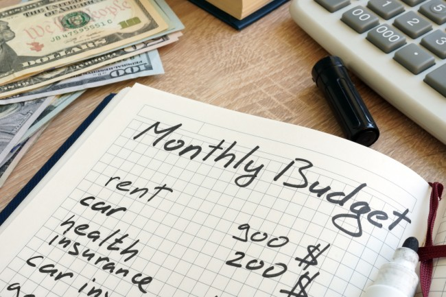 Note pad with monthly budget calculations and money.