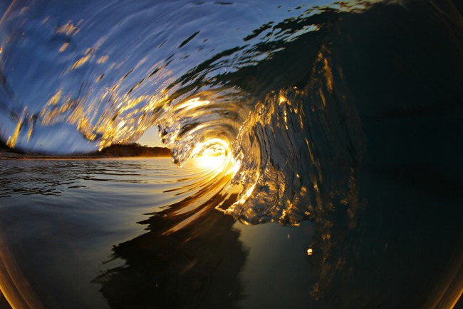 A barreling wave illuminated by the setting sun.