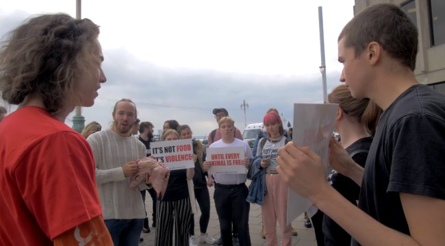 protester eats raw pig's head outside vegan festival in stand-off with animal rights activists