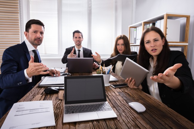 Portrait Of Shocked Young Businesspeople Sitting In Office