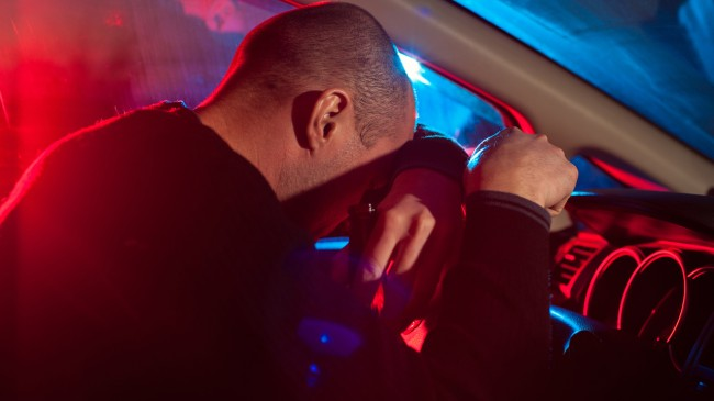 Upset drunk driver is caught driving under alcohol influence. Man covering his face from police car light.