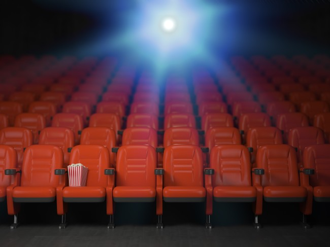 Cinema and movie theater concept background. Empty rows of red seats with popcorn.
