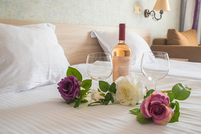 flowers and wine on hotel bed