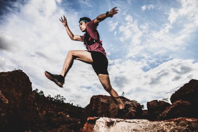 trail runner jumping rocks