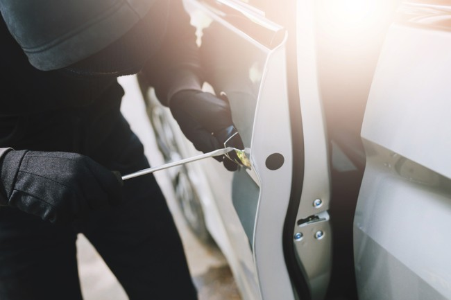 Close up hand pulling the handle of a car thief wearing black clothes and glove stealing automobile trying door handle to see if vehicle is unlocked trying to break into. car theft concept.