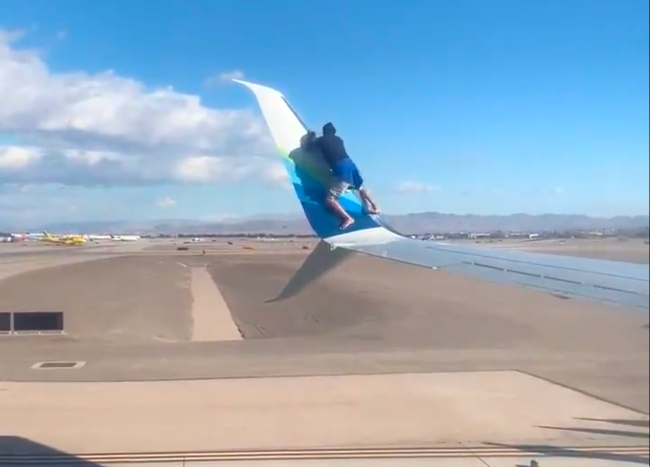 Guy Climbs On Wing Of Plane