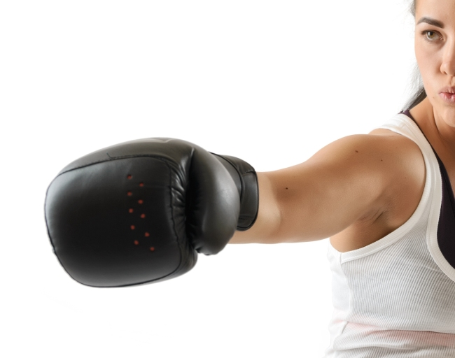 Boxer woman during boxing exercise making direct hit in black