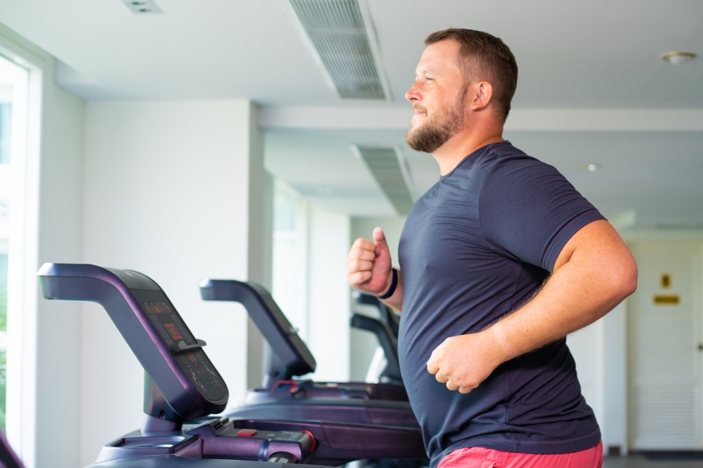 Dad Bod guy running on treadmill