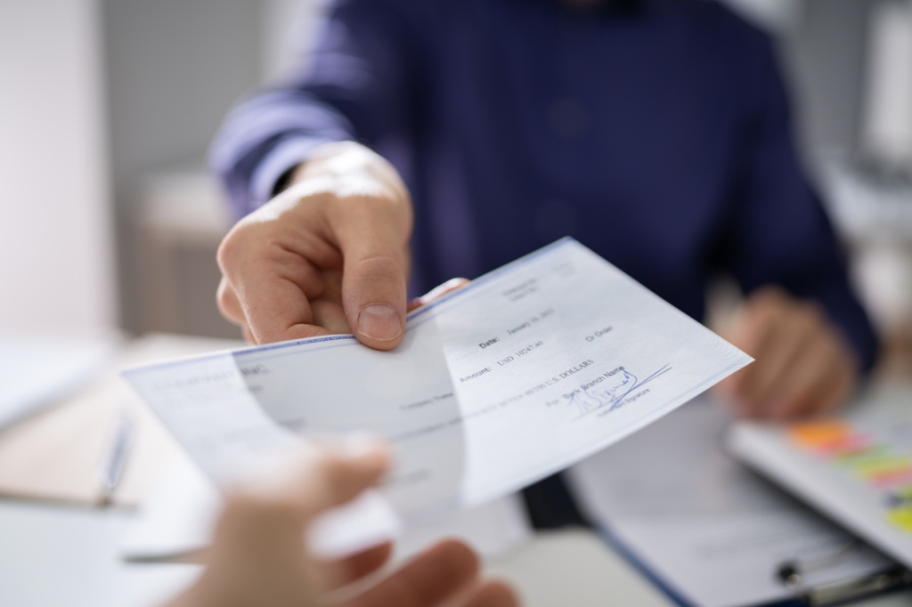person handing paycheck