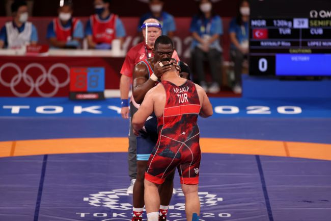 CHIBA, JAPAN - AUGUST 01: Riza Kayaalp (red) of Team Turkey and Mijain Lopez Nunez (blue) of Team Cuba hug each other after competing in menâs wrestling greco-roman semi final match during Tokyo 2020 Olympic Games at Makuhari Messe Hall in Chiba, Japan on August 01, 2021.