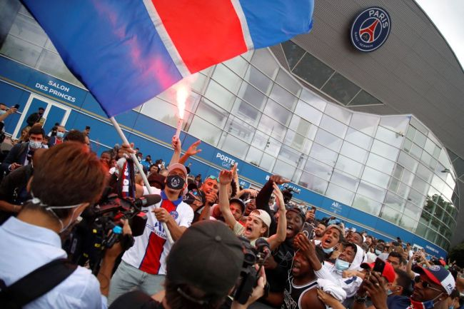 """Supporters cheer outside French football club Paris Saint-Germain's (PSG) Parc des Princes stadium in Paris on August 10, 2021, after Argentinian football player Lionel Messi landed in Le Bourget airport near Paris. - Asked by reporters at Barcelona's El Prat airport if the Argentine star would later on sign with the French club, Jorge Messi, the father and player's agent, said: """"Yes""""."""