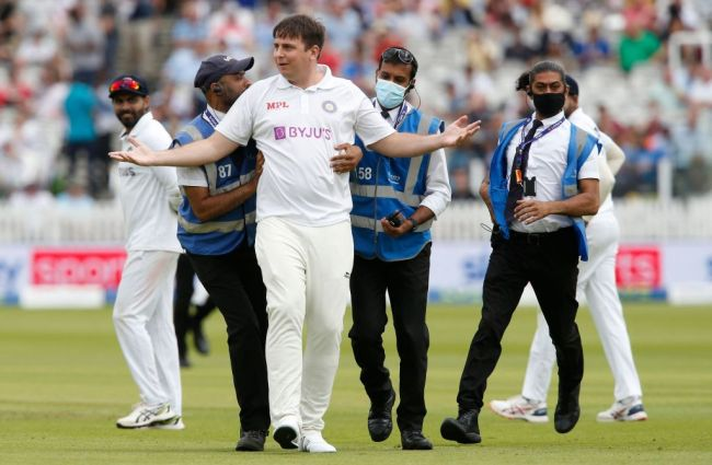 A pitch invader is escorted off of the the pitch on the third day of the second cricket Test match between England and India at Lord's cricket ground in London on August 14, 2021.