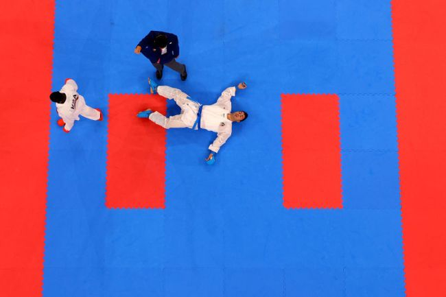 TOKYO, JAPAN - AUGUST 07: Sajad Ganjzadeh (R) of Team Iran lays on the tatami after being struck by Tareg Hamedi of Team Saudi Arabia during the Men's Karate Kumite +75kg Gold Medal Bout on day fifteen of the Tokyo 2020 Olympic Games at Nippon Budokan on August 07, 2021 in Tokyo, Japan.